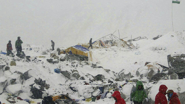 In this photo provided by Azim Afif people approach the scene after an avalanche triggered by a massive earthquake swept across Everest Base Camp, Nepal on Saturday, April 25, 2015. (Photo by Azim Afif/AP Photo)
