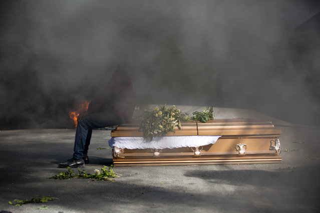 A demonstrator sits on the coffin containing the body of a protester who was killed during previous protests in Port-au-Prince, Haiti, Monday, March 4, 2019. Protesters are angry about skyrocketing inflation and the government's failure to prosecute embezzlement from a multi-billion Venezuelan program that sent discounted oil to Haiti. (Photo by Dieu Nalio Chery/AP Photo)