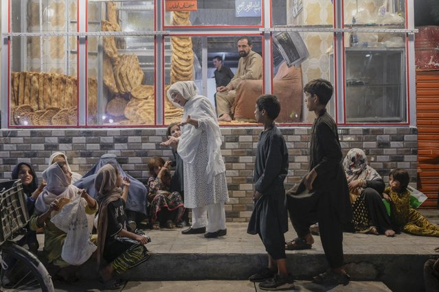 A woman talks to young people in need after giving them bread in front of bakery in Kabul on September 19, 2021. (Photo by Bulent Kilic/AFP Photo)