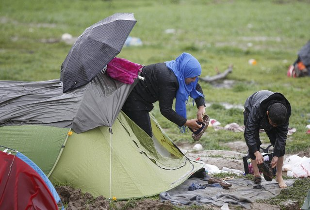 Migrants clean their boots from mud at a makeshift camp on the Greek-Macedonian border, near the village of Idomeni, Greece March 10, 2016. (Photo by Stoyan Nenov/Reuters)
