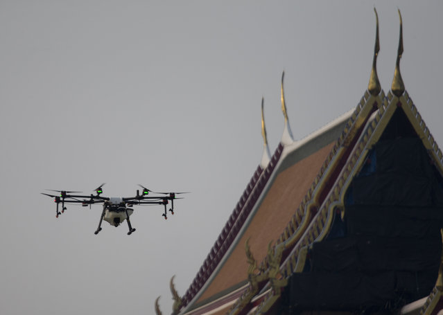 Drone pilots fly a water-spraying drone over the Suthat Temple in Bangkok, Thailand, Thursday, Jan. 31, 2019. Drone pilots prepare to launch a water-spraying drone before flying over the Suthat Temple in Bangkok, Thailand, Thursday, January 31, 2019. A fleet of drones, trucks and small planes are spraying water to try to reduce dust around Bangkok while the governor invited critics to brainstorm better ideas to improve the air quality in the Thai capital. (Photo by Sakchai Lalit/AP Photo)