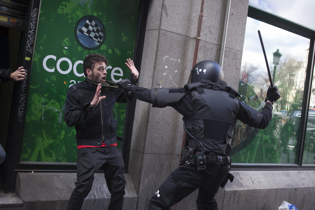 A riot police officer uses his baton against a demonstrator during clashes following an eviction of a chronically ill 54-year old neighbour from his home in Madrid, Spain, Friday, January 31, 2014. Harsh repossession laws  have led to hundreds of thousands of evictions during the country's deep recession as more than 350,000 people in Spain have received eviction orders since 2008 because they were unable to make mortgage payments. (Photo by Gabriel Pecot/AP Photo)