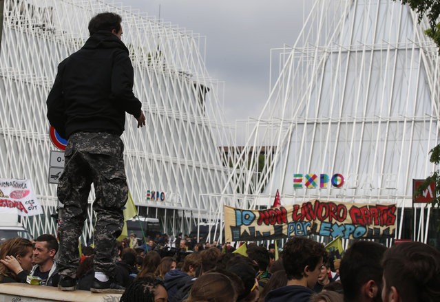 """Demonstrators gather at the Expo gate as a banner reads in Italian: """"I don't work for Expo for free"""" during a protest against Expo 2015 in Milan, Italy, Thursday, April 30, 2015. (Photo by Luca Bruno/AP Photo)"""