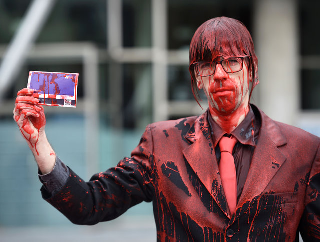 """A member of """"Platform Against BBVA"""" covered with red paint holds a BBVA card as he protests in front of Euskalduna Palace where the Spanish bank held its 2016 BBVA Share Holders meeting, in the northern Spanish Basque city of Bilbao, on March 11, 2016. The platform denounces the allegedly connection between the BBVA bank and the arms industry. The protesters covered themselves with red paint symbolising, according to them, the blood of the victims of the deadly business of the bank. (Photo by Ander Gillenea/AFP Photo)"""