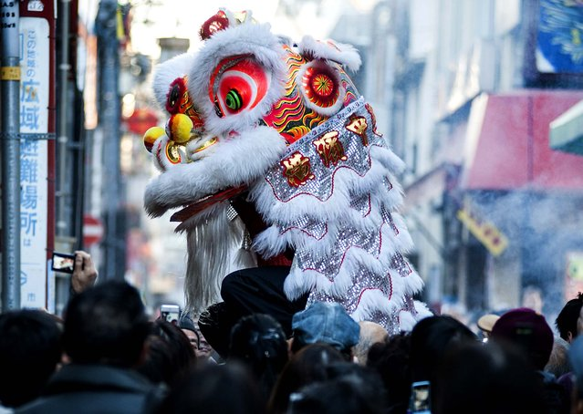 A lion dance is performed in front of a Chinese restaurant in Yokohama, Japan. (Photo by Keith Tsuji/Getty Images)