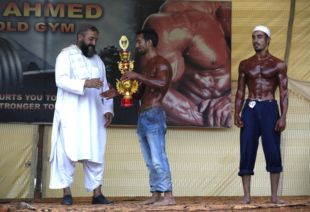 A participant is given his trophy by an elder during a local bodybuilding and fitness championship in Karachi, Pakistan March 13, 2016. (Photo by Akhtar Soomro/Reuters)