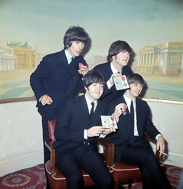 The Beatles show their MBE medals during a news conference in London, England, October 26, 1965.  They were made members of the Order of the British Empire by the Queen of England at Buckingham Palace.  The quartet are, standing, George Harrison, left, John Lennon; seated, Paul McCartney, left, and Ringo Starr.  (Photo by AP Photo)