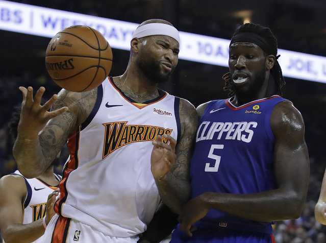 Golden State Warriors' DeMarcus Cousins, left, reacts to a foul called against him beside Los Angeles Clippers' Montrezl Harrell (5) in the first half of an NBA basketball game Sunday, April 7, 2019, in Oakland, Calif. (Photo by Ben Margot/AP Photo)