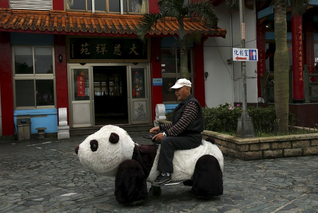 An elderly man sits on a panda-shaped ride inside a Guanine temple in Keelung, Taiwan March 20, 2016. (Photo by Tyrone Siu/Reuters)