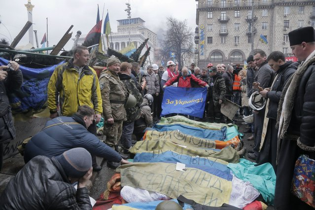 """Activists and priests pay respects to protesters who were killed in clashes with police, a flag held by one activist reads """"For Ukraine"""" in Kiev's Independence Square, the epicenter of the country's current unrest, Kiev, Ukraine, Thursday, February 20, 2014. (Photo by Efrem Lukatsky/AP Photo)"""