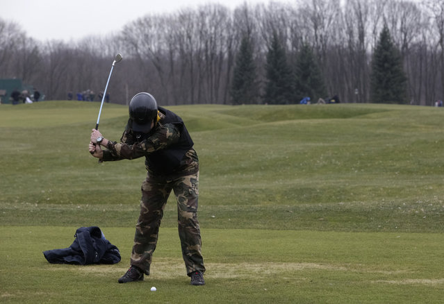 A man plays golf as anti-government protesters walk on the grounds of the Mezhyhirya residence of Ukraine's President Viktor Yanukovich in the village Novi Petrivtsi, outside Kiev February 22, 2014. (Photo by Konstantin Chernichkin/Reuters)