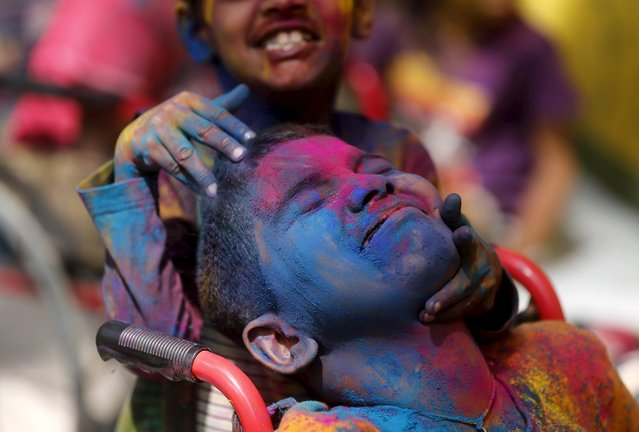 Disabled children cover each other in coloured powder during Holi celebrations in Mumbai, India, March 23, 2016. (Photo by Shailesh Andrade/Reuters)