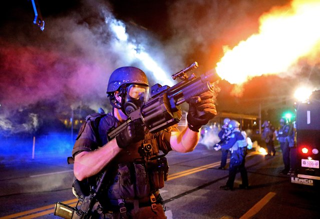 This August 18, 2014 photo by St. Louis Post Dispatch photographer David Carson, a member of the St. Louis County Police tactical team fires tear gas into a crowd of people in response to a series of gunshots fired at police during demonstrations in Ferguson. (Photo by David Carson/St. Louis Post-Dispatch via AP Photo)