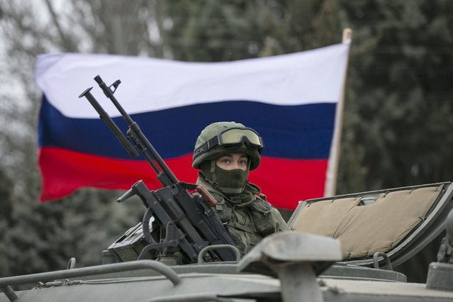 A pro-Russian man (not seen) holds a Russian flag behind an armed servicemen on top of a Russian army vehicle outside a Ukrainian border guard post in the Crimean town of Balaclava March 1, 2014. Ukraine accused Russia on Saturday of sending thousands of extra troops to Crimea and placed its military in the area on high alert as the Black Sea peninsula appeared to slip beyond Kiev's control. (Photo by Baz Ratner/Reuters)