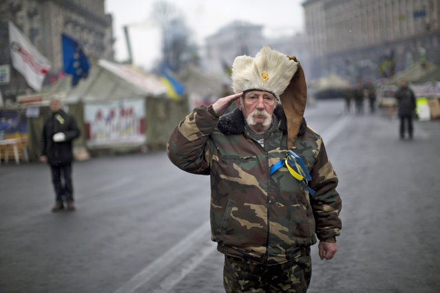 An anti-Yanukovych protester salutes as the Ukrainian national anthem is played at Kiev's Independence Square, Ukraine, Monday, March 3, 2014. The U.S. and its allies are weighing sanctions on Moscow and whether to bolster defenses in Europe in response to Russia's military advances on Ukraine. (Photo by Emilio Morenatti/AP Photo)
