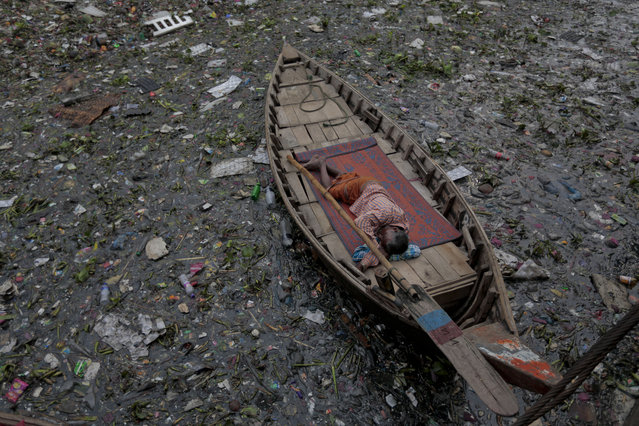 A Bangladeshi man sleeps on a boat anchored on the highly polluted River Buriganga in Dhaka, Bangladesh, Monday, March 28, 2016. Buriganga River has become a large mass of extremely polluted water, contaminated by hazardous pollutants such as industrial and household waste, sewage, medical waste, oil, plastics, and dead animals. (Photo by A.M. Ahad/AP Photo)