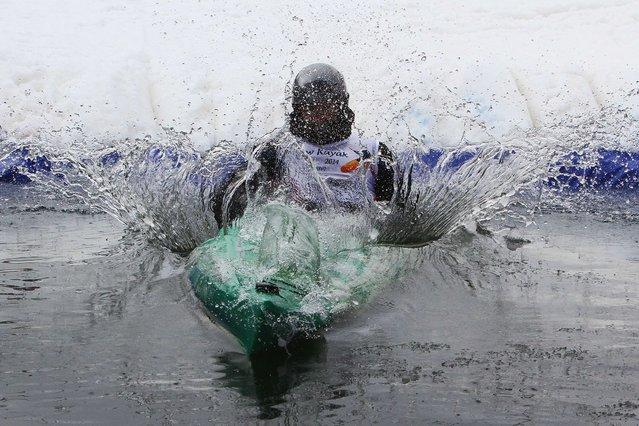 A participant in a Snow Kayak race competes at the alpine skiing track in Druskininkai, Lithuania on March 1, 2014. (Photo by Petras Malukas/AFP Photo)