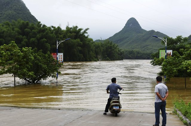 People look at a partially flooded street after heavy rainfall hit Luocheng Mulao Autonomous County, Guangxi Zhuang Autonomous Region, China, May 15, 2015. Torrential rain and thunderstorms swept parts of south China on Thursday, while the National Meteorological Center (NMC) on Friday issued a yellow alert for downpours for 11 provinces, local media reported. (Photo by Reuters/Stringer)