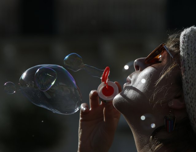 A woman blows soap bubbles during an activity organised by various non-governmental organisations to mark International Human Rights Day in Valletta December 14, 2014. (Photo by Darrin Zammit Lupi/Reuters)