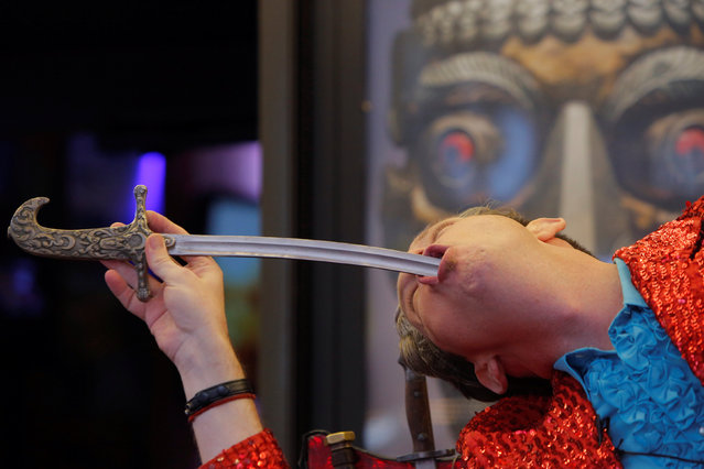 """Sword swallower Fred """"The Great Fredini"""" Kahl swallows a sword at Ripley's Believe It or Not! Times Square Odditorium to celebrate World Sword Swallower's Day in Manhattan, New York, U.S., February 25, 2017. (Photo by Andrew Kelly/Reuters)"""
