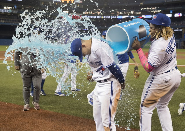 Toronto Blue Jays' Cavan Biggio gets a bucket shower from teammate Vladimir Guerrero Jr. during a post-game interview after the Jays defeated the San Diego Padres 10-1 in a baseball game in Toronto, Sunday, May 26, 2019. (Photo by Fred Thornhill/The Canadian Press via AP Photo)