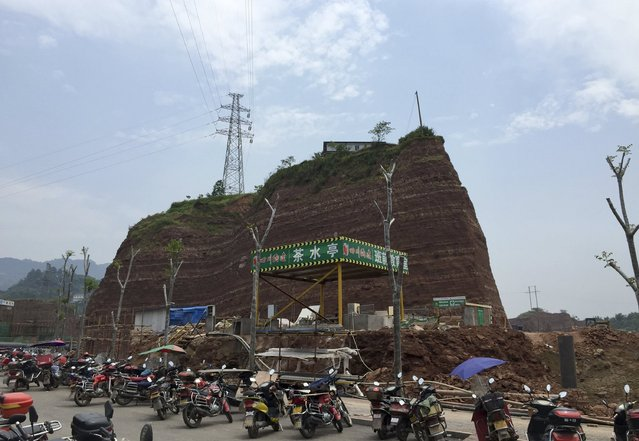 A nail house sits atop a mound, next to a construction site for a new residential area, in Yibin, Sichuan province, China, May 19, 2015. According to local media, owners of the nail house refused to move as they couldn't reach an compensation agreement with the authority in charge of the demolition. The house is now sitting on a mound about 20 metres above ground as the land around the house were dug out by the developer. (Photo by Reuters/Stringer)