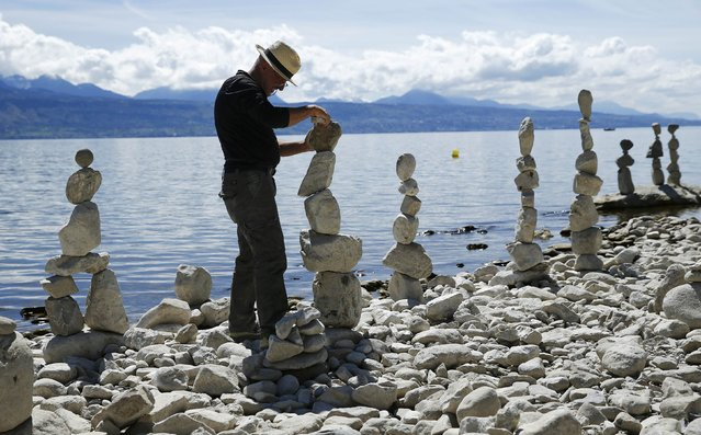 Swiss land art artist Daniel Dunkel builds a cairn on the shore of Lake Leman in Lutry, near Lausanne, Switzerland, April 14, 2016. (Photo by Denis Balibouse/Reuters)