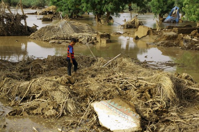 A boy walks on the wreckage of huts destroyed by floods following heavy rain in a village in Yemen's Red Sea province of Houdieda April 15, 2016. (Photo by Abduljabbar Zeyad/Reuters)