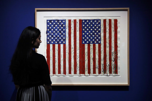 "A British Museum representative poses for photographs next to ""Flag I"" by Jasper Johns which features in ""The American Dream: pop to the present"" exhibition during a media photocall at the British Museum in London, Monday, March 6, 2017. The exhibition, which opens to the public from March 9 and runs until June 18, charts modern and contemporary print making. (Photo by Matt Dunham/AP Photo)"