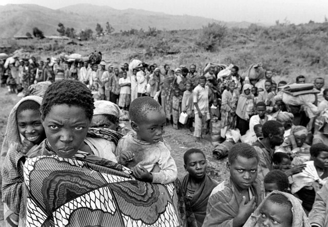 Thousands of refugees line the road in Sake, Zaire, waiting for transport to Rwanda after their long exodus. About 5,000 refugees were on the road; 1996. (Photo by Carol Guzy/The Washington Post)