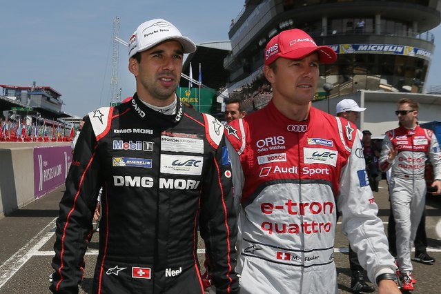 Porsche 919 No18 Swiss driver Neel Jani, left, walks on the race track with Audi No7 Swiss driver Marcel Fassler, right, before the start of the 83rd 24-hour Le Mans endurance race, in Le Mans, western France, Saturday, June 13, 2015. (AP Photo/David Vincent)