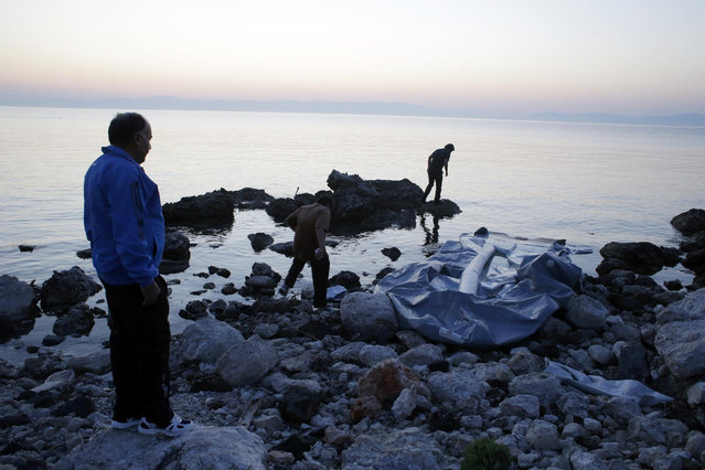 Syrian migrants look for their missing passports in the sea after their arrival on a small boat, right, from a Turkish coast to the Greek island of Lesvos in Mytilene, on Wednesday, June 17, 2015. Around 100,000 migrants have entered Europe so far this year as Italy and Greece have borne the brunt of the surge with many more migrants expected to arrive from June through to September. (AP Photo/Thanassis Stavrakis)