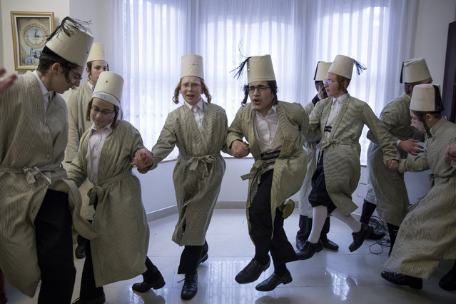 Young Jewish men dance around a local business man's home during the annual Jewish holiday of Purim on March 12, 2017 in London, England. Purim is celebrated by Jewish communities around the world with parades and costume parties. Purim commemorates the defeat of Haman, the advisor to the Persian king, and his plot to massacre the Jewish people, 2,500 years ago, as recorded in the biblical book of Esther. (Photo by Dan Kitwood/Getty Images)