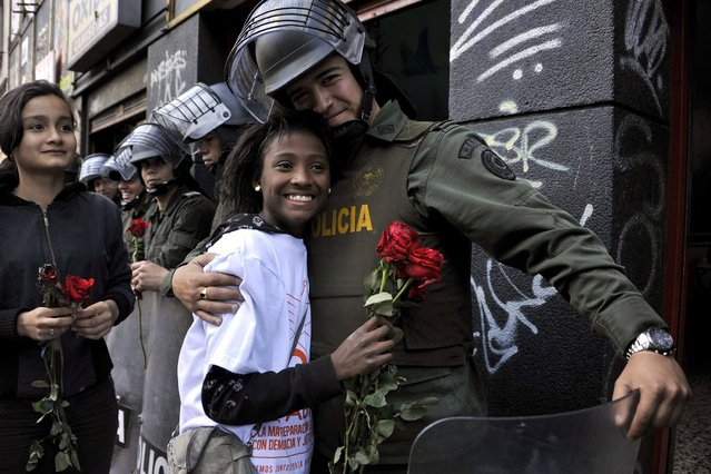 A riot policeman hugs an activist who gave him a rose during the National Day of Remembrance and Solidarity with Victims of the Armed Conflict, in Bogota, Colombia on April 9, 2014. In Colombia, the armed conflict which involved leftist guerrillas, right-wing paramilitaries, military and drug gangs has left 6 million affected, of which at least 5 million are displaced according to the most recent UN human rights report. (Photo by Guillermo Legaria/AFP Photo)