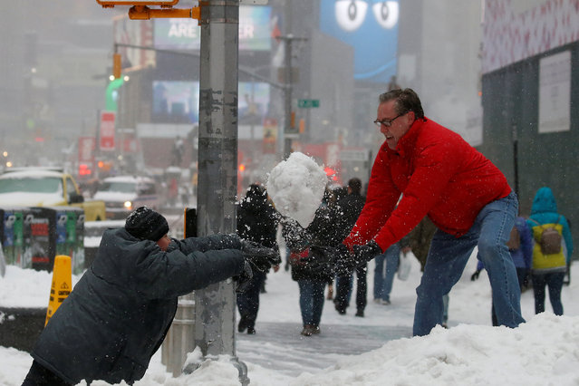 A man and child take part in a snowball fight in Times Square during a snowstorm, New York, U.S., March 14, 2017. (Photo by Carlo Allegri/Reuters)