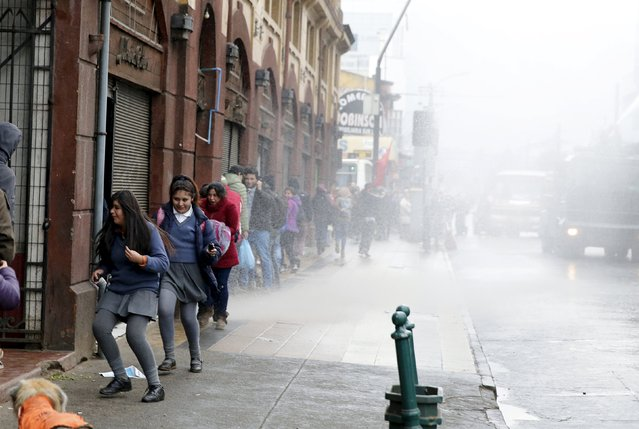 Students run away from a jet of water from a riot police water cannon during a demonstration for education reform, in Temucho June 25, 2015. (Photo by Andres Stapff/Reuters)