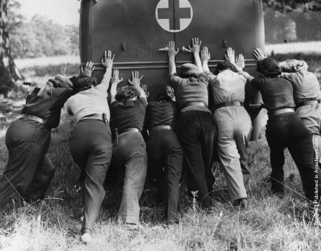 1940: Members of the Women's Mechanised Transport Corps push an ambulance out of some rough ground