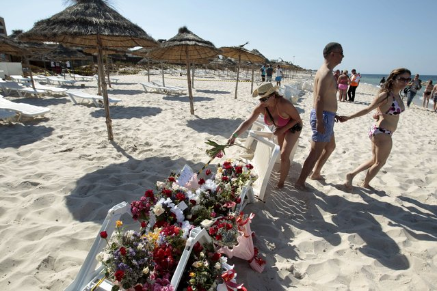 A tourist places flowers at the beachside of the Imperiale Marhabada hotel, which was attacked by a gunman in Sousse, Tunisia, June 27, 2015. Tour companies were evacuating thousands of foreign holidaymakers from Tunisia on Saturday, a day after a gunman killed 39 people as they lounged at the beach in an attack claimed by Islamic State. (Photo by Zoubeir Souissi/Reuters)