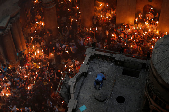 Worshippers hold candles as another prays during the Christian Orthodox Holy Fire ceremony at the Church of the Holy Sepulchre in Jerusalem's Old City April 30, 2016. (Photo by Ammar Awad/Reuters)