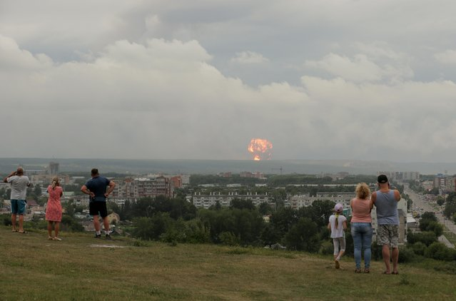 People watch flame and smoke rising from the site of blasts at an ammunition depot near the town of Achinsk in Krasnoyarsk region, Russia, August 5, 2019. The accident prompted evacuation of the settlements located within the radius of 20 km from the village, several people have been taken to hospital with injuries. (Photo by Dmitry Dub/Reuters)