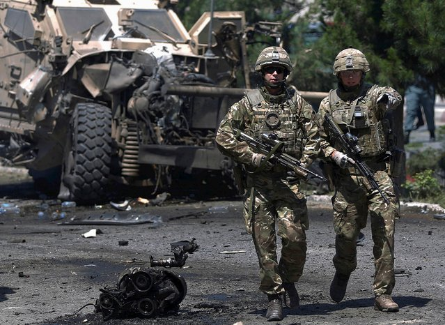 NATO soldiers walk at the site of a suicide bomb attack in Kabul, Afghanistan June 30, 2015. (Photo by Ahmad Masood/Reuters)