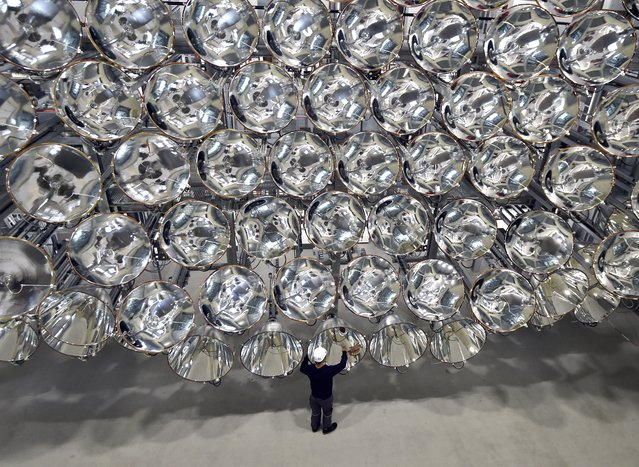 Employee, Volkmar Dohmen, stands in front of Xenon arc lamps that form a large artifical sun at the German Aerospace Center (DLR) in Juelich, Germany, 21 March 2017. A large artifical sun called Synlight can emit up to 10,000 times the intensity of the sun's light. (Photo by Caroline Seidel/Picture-alliance/DPA/AP Images)