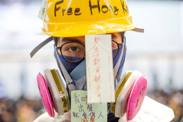 Anti-extradition bill demonatrator wears a helmet and a mask during a protest at the arrival hall of Hong Kong International Airport in Hong Kong, China August 9, 2019. (Photo by Thomas Peter/Reuters)