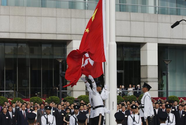Participants attend the flag raising ceremony to mark the 18th anniversary of the Hong Kong handover to China in Hong Kong, Wednesday, July 1, 2015. (Photo by Kin Cheung/AP Photo)