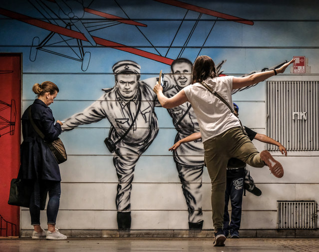 A woman instructs a boy on how to pose for pictures in front of a mural depicting Soviet pilot Valery Chkalov – who took a non-stop flight over the Arctic and landed in the US state of Washington in 1937 – at Chkalovskaya metro station in Moscow on August 14, 2019. (Photo by Yuri Kadobnov/AFP Photo)