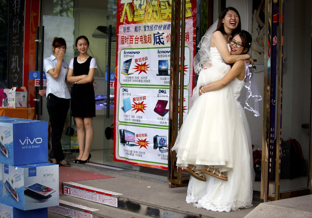 Li Tingting, second from right, laughs as she is lifted off the ground by her wife Teresa Xu, right, outside of a beauty salon where the two were preparing for their wedding as clerks from an adjacent shop look on in Beijing, Thursday, July 2, 2015. (Photo by Mark Schiefelbein/AP Photo)