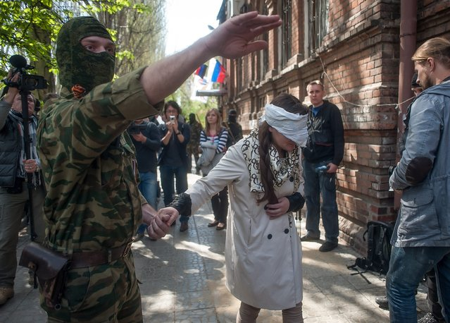 A masked man in military fatigues brings a blindfolded Irma Krat, arrested and held by pro-Russian protestors before her meeting with journalists near of occupied police station in Slaviansk, Ukraine, 21 April 2014. Pro-Russian activists are demanding broader autonomy from Kiev and closer ties to Russia. (Photo by Roman Pilipey/EPA)