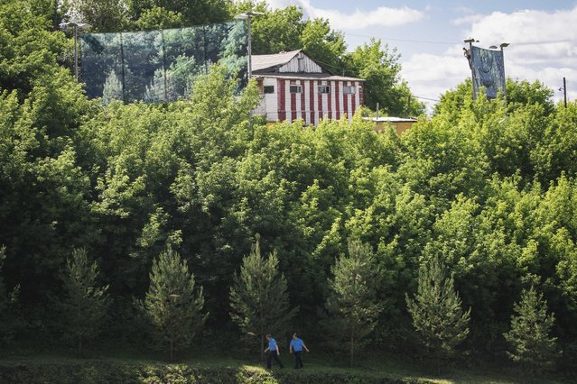 In this photo taken on Sunday, July  5, 2015, security officers walk near a Congress Hall which will host SOC (Shanghai Cooperation Organization) and BRICS (Brazil, Russia, India, China and South Africa) summits July 7 to July 9, 2015. A house on a hill is partially covered with paintings of a forest, to hide it. (Photo by Vadim Braydov/AP Photo)