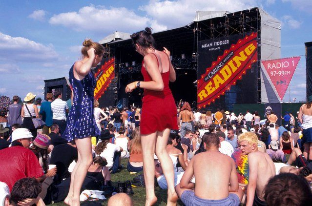 View of stage at Reading Festival, United Kingdom in 1970 showing festival-goers sitting on grass and standing dancing. (Photo by Nicky J. Sims/Redferns)