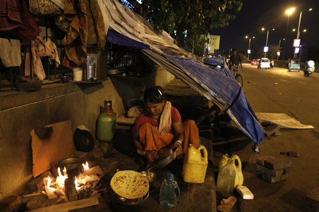 An Indian woman prepares food outside her makeshift dwelling on a pavement in Ahmadabad, India, Friday, July 3, 2015. India has released new socio-economic and caste census data on Friday that covers the period between 2011 and 2013 to show the wealth, living conditions and other details of the country's 1.2 billion people. (Photo by Ajit Solanki/AP Photo)